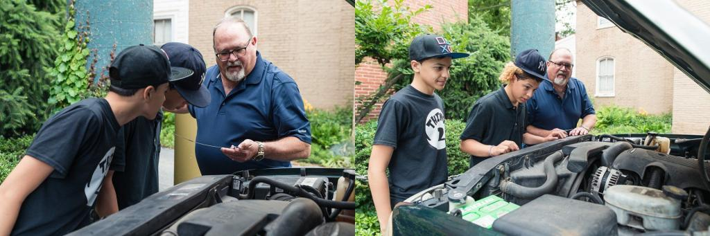 Volunteers show boys how to check the oil in the car.
