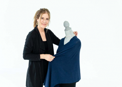 Boutique owner draping poncho on mannequin